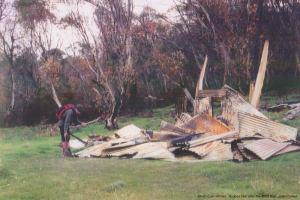 Photo Colin Brown. John Purves examining Boobee Hut burnt after the 2003 fires