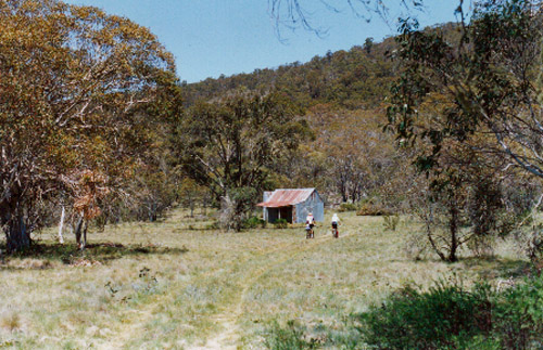 Photo of two cyclists on a foot track approaching Bill Jones Hut