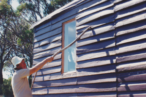Dennis Hall poking poor weatherboards; &#169 K. Mathers 1994