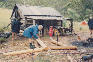 Vickerys Hut Workparty, Leonie Hamilton supervising the trimming of logs, 1987.